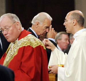 Joe Biden, militant pro-abortion and pro-sodomy psychopath oligarch,  receiving the Eucharist from Cardinal Timothy Dolan at St. Patrick's Cathedral in NYC.
