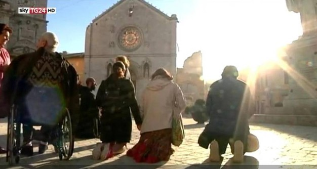 People praying in Norcia, Italy